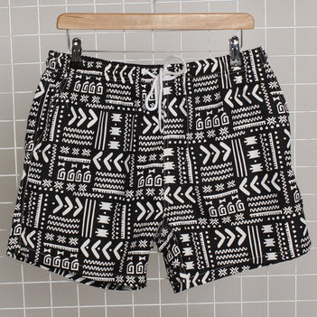 black swim shorts with a white aztec pattern print on a clothes hangar